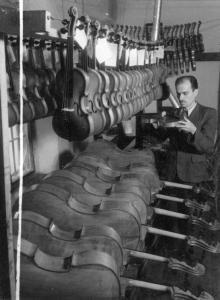 Мастер Одесской фабрики смычковых инструментов И.П. Кочмарчук осматривает готовые инструменты. 5.I.1952 г. Одесса А. Фатеев (855)