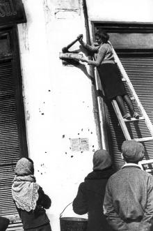 Одесса, ул. К. Маркса. Жительница Одессы снимает табличку с названием улицы, переименованной во время фашистской оккупации города. Фото Марка Редькина. 24 апреля 1944 г.
