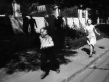Забор волейбольной площадки на месте будущей школы № 117. Кадр из фильма «Неподдающиеся». Герои бегут по ул. Ленина, за ними ул. Р. Люксембург. Киностудия «Мосфильм», 1959 г.